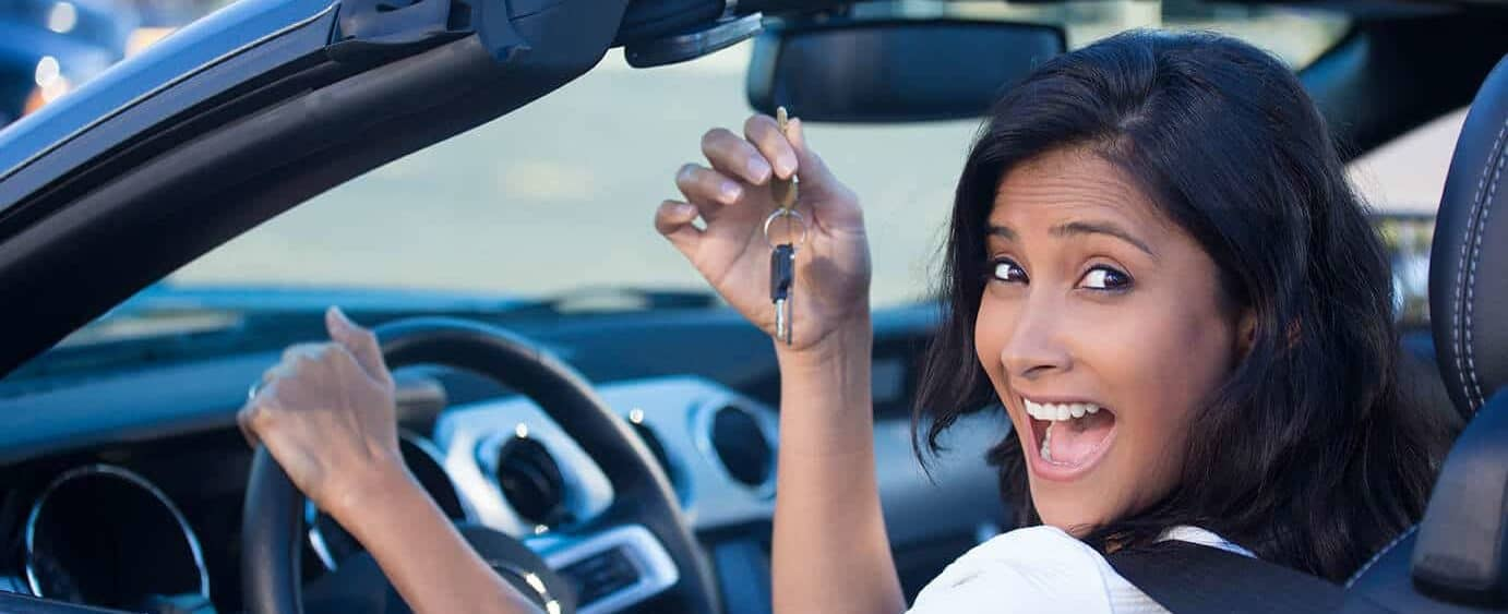 Happy woman in a brand new car holding her keys.