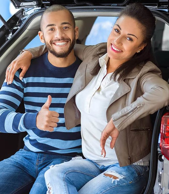 Happy couple sitting in the back of a new SUV