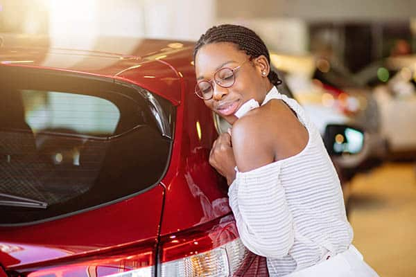 Happy African American woman hugging a car.