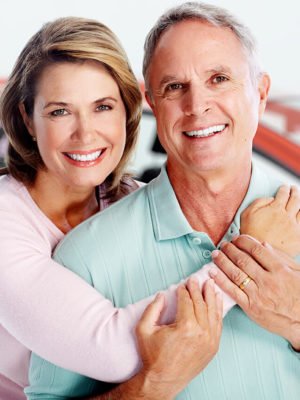 Older couple holding each other in a car dealership.