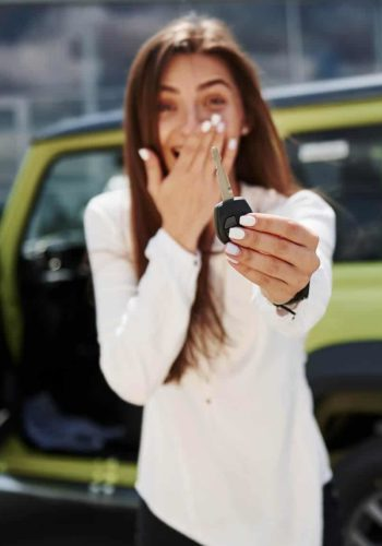 Happy woman holding keys in front of her new car.