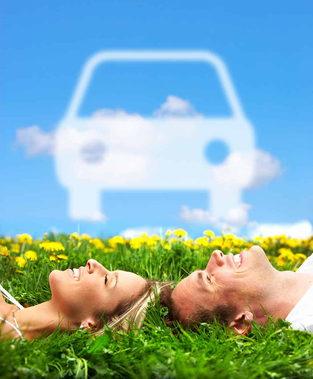 Two people laying on the ground with an image of a car in the clouds.